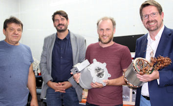 """Beim Rundgang durch die """"Denkerschmiede"""" der Dynamic E Flow GmbH präsentierten Nikolaus Schweinert (ganz links), Michael Anton Naderer (2. v. links) und Manuel Hartong (rechts) dem Abgeordneten im Haus entwickelte Prototypen."""